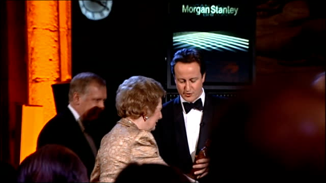 david cameron presents margaret thatcher with a lifetime achievement award; thatcher in audience watching film about her / thatcher rising then along... - 生涯功労賞点の映像素材/bロール