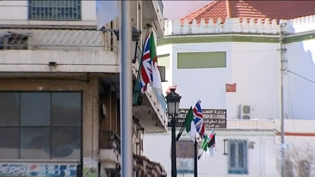 david cameron visits algeria and offers support against terrorism algiers union jack and algerian flags hanging outside building zoom out street... - アルジェリア人質事件点の映像素材/bロール