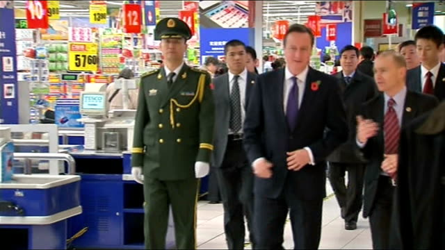 david cameron visits beijing tesco and interview *** warning tesco's employee / david cameron walking through shop on visit to beijing tesco's store... - tesco点の映像素材/bロール