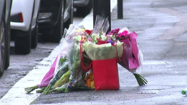nhs worker stabbed outside his home england london ext gv bouquets of flowers / floral tributes at base of street lamp - crime and murder stock-videos und b-roll-filmmaterial