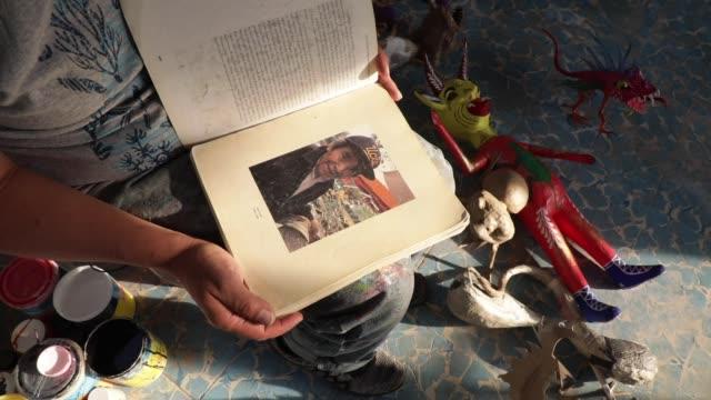 "vídeos de stock e filmes b-roll de david linares poses showing the pages of the book entitled ""en calavera"" dedicated to the linares family during a day of work at david linares studio... - espiritualidade"