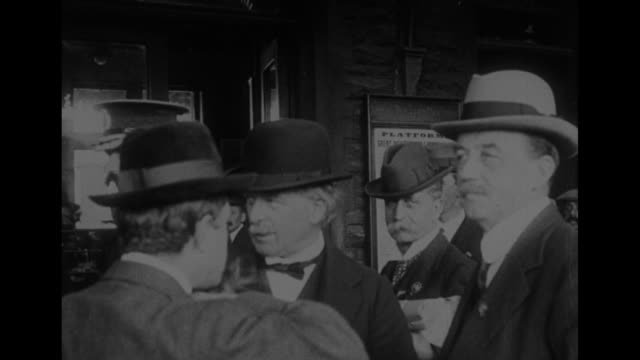 ms david lloyd george wearing bowler hat in center of group of men standing on train station platform a british military officer stands nearby / note... - vox populi stock videos & royalty-free footage