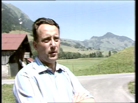 david niven tribute; switzerland: chateau d'oex gv mountains and road r-l to nivens house in trees cms ext. wall of house bv man at door of niven's... - 俳優 ロジャー・ムーア点の映像素材/bロール