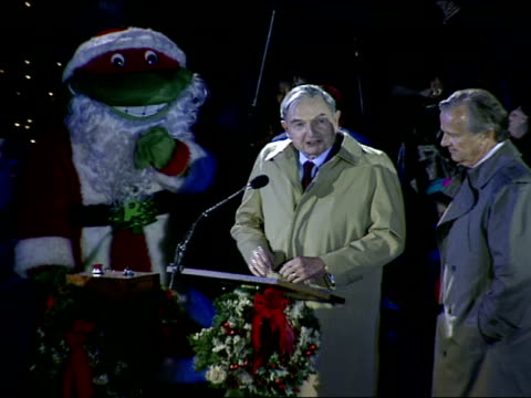 david rockefeller, sr. behind microphone reading script about the un flags around the center. - illuminazione dell'albero di natale del rockefeller center video stock e b–roll