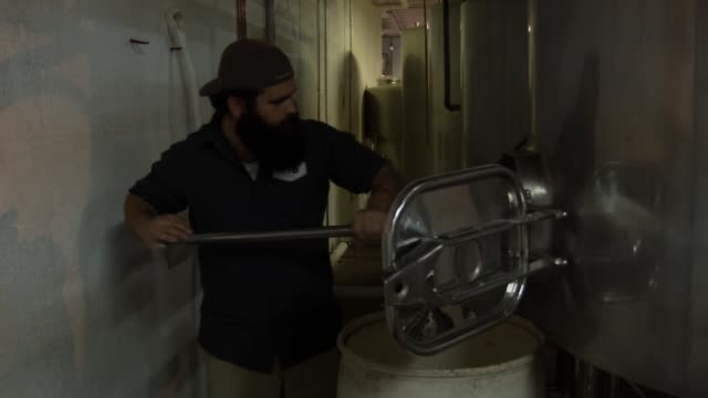 david rodriguez, a beer brewer, uses a rake to pull the malted barley from the mash tun at wynwood brewing company on april 25, 2014 in miami,... - マッシュポテト点の映像素材/bロール