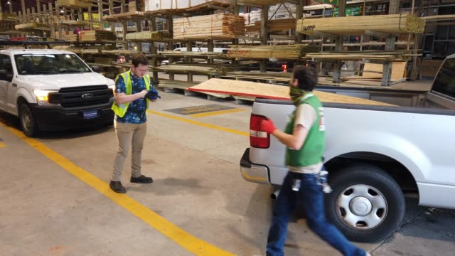 david rosenbaum jr and devlin cudd load plywood into vehicles as people purchase supplies at the stine hardware store before the possible arrival of... - eventuell stock-videos und b-roll-filmmaterial