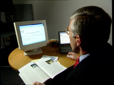david shayler arrested lib london int jack straw mp seated at computer looking at mi5 website mi5 glossy brochure held and flicked thru - jack straw stock videos & royalty-free footage