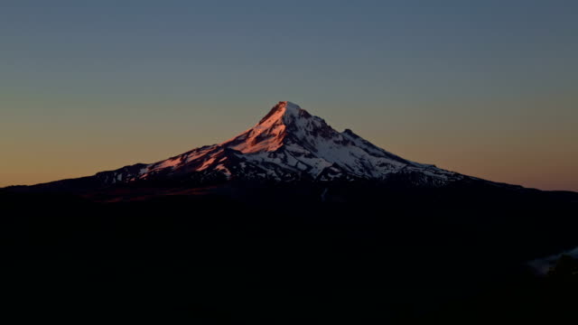 Dawn alpenglow on snowy mountain Mt. Hood in summer from lost lake butte North Face