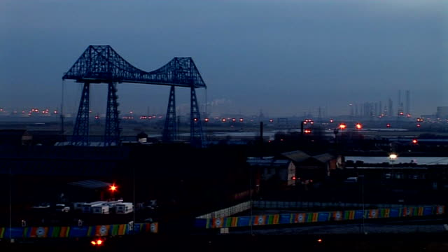 vídeos de stock, filmes e b-roll de dawn breaking over industrial landscape and tees transporter bridge stockton-on-tees: pedestrians crossing infinity bridge over river people walking... - tees river