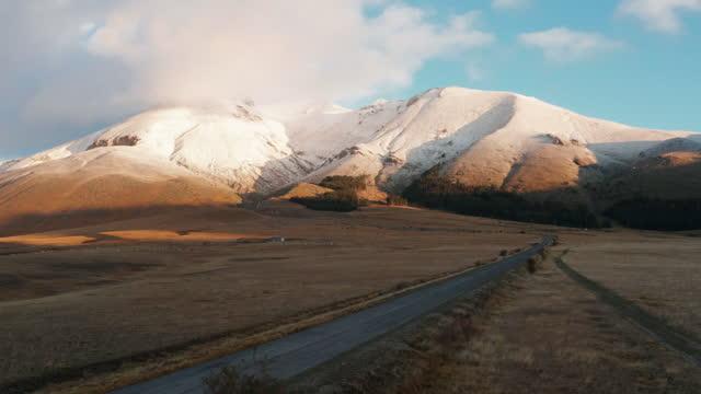 morgendämmerung in campo imperatore mit einer herde von kühen und verschneiten bergen im hintergrund - herde stock-videos und b-roll-filmmaterial