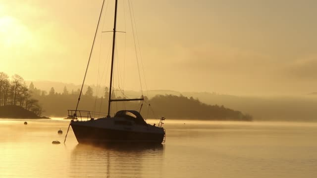 Dawn mist in winter over sailing boats on Lake Windermere at Ambleside, in the Lake District National Park, Cumbria, UK.