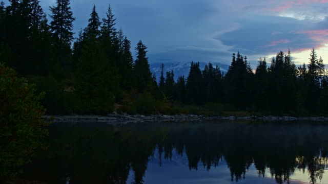 Dawn reflection of Mt. Hood covered in clouds on Mirror Lake in the fall forest