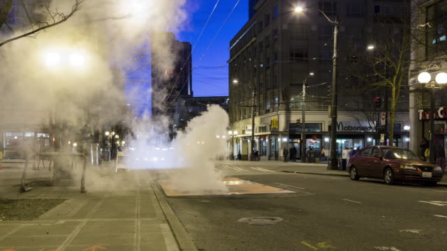 A dawn time lapse of early morning traffic in downtown Seattle, focused on steam escaping through a vent in the street.