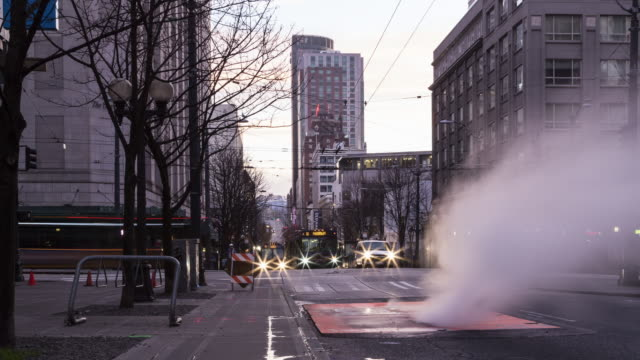 A dawn time lapse of early morning traffic in downtown Seattle, focused on steam escaping through a vent in the street and featuring water filling up the cracks in the sidewalk.