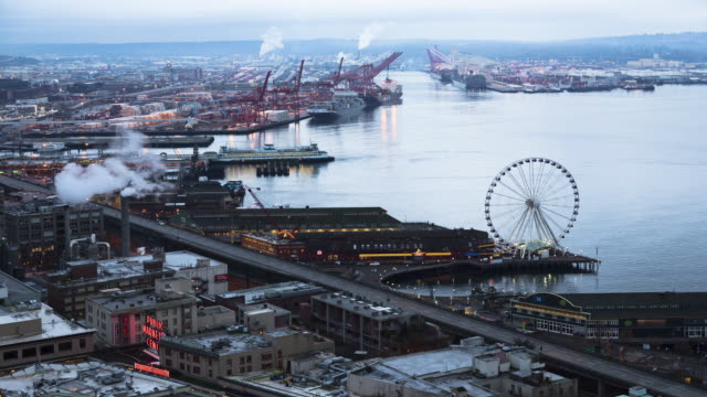 A dawn time lapse of the Seattle waterfront featuring ferries arriving and departing from Colman dock and the Seattle Great Wheel in the midfield, and Harbor Island in the background.