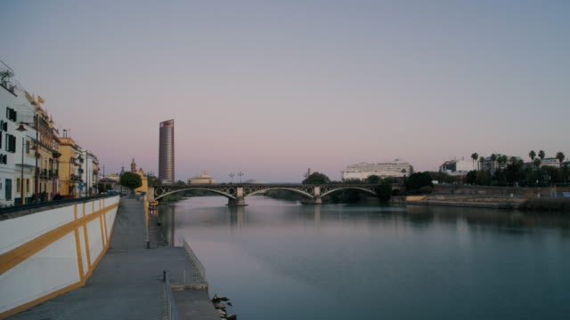 stockvideo's en b-roll-footage met dawn to day time-lapse of the triana bridge, seville, spain - puente