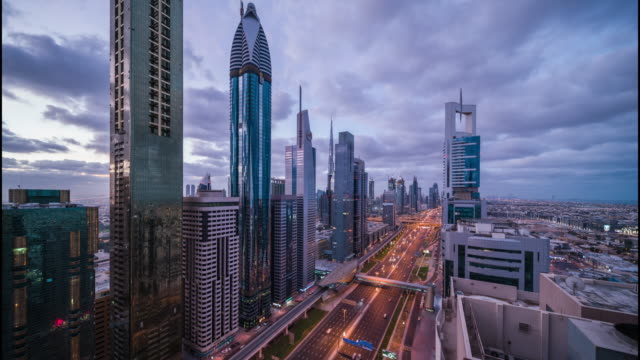 dawn to day transition of dubai futuristic downtown cityscape with skyscrapers and urban roads - dawn to day stock videos & royalty-free footage