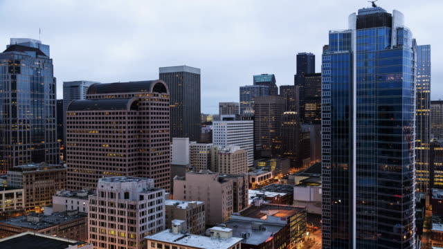 A dawn to daytime time lapse of the cityscape in downtown Seattle with low, grey clouds overhead and minimal motion.