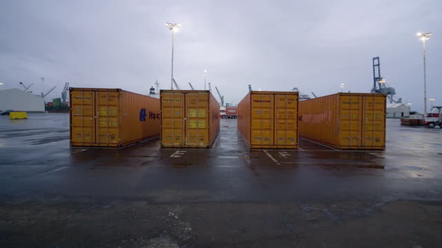 TL WS Dawn turning to day as forklifts load cargo containers with large rolls of paper and straddle carriers pick them up at Ports of Auckland/ Auckland, New Zealand