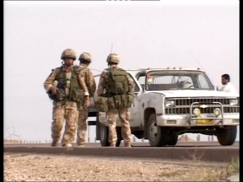 Day 12 Lunchtime news POOL CMS British soldiers crouched down as helicopter lands behind MS Soldiers manning vehicle checkpoint AT NIGHT/GREEN...