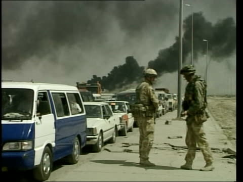vídeos y material grabado en eventos de stock de day 13 lunchtime news pool basra cms british soldier along on patrol as smoke billows in sky behind ms british soldiers standing next line of traffic... - basra
