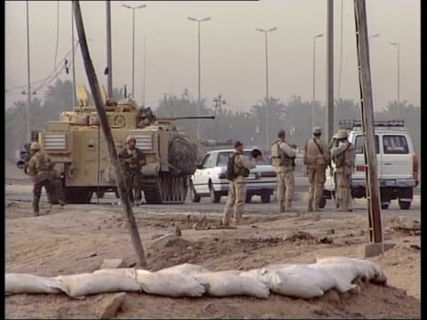 news; 17.20: juliet bremner iraq: basra: ext gv city gates to basra cms statue of president saddam hussein british army armoured vehicle parked next... - major road bildbanksvideor och videomaterial från bakom kulisserna