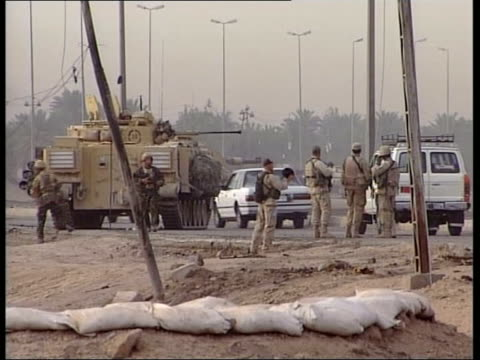 news; 21.00: juliet bremner iraq: basra: ext gv city gates to basra cms statue of president saddam hussein british army armoured vehicle parked next... - major road bildbanksvideor och videomaterial från bakom kulisserna