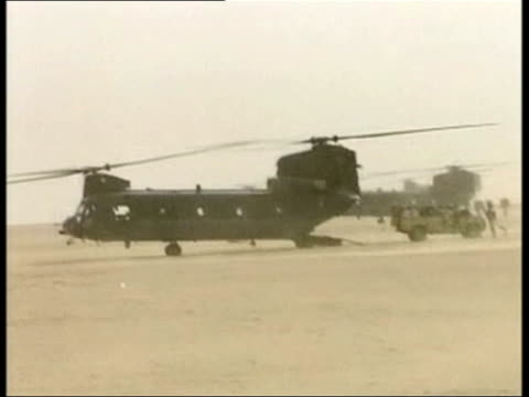 Day 2 News at Nine special POOL KUWAIT EXT Royal Marines away towards helicopter Line of Marines soldiers boarding helicopter as sand blowing around...
