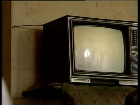 evening news bulletin; tv set in cafe showing saddam hussein on iraqi tv cms local men, smoking pipes, as watching tv - television show stock videos & royalty-free footage