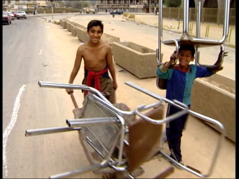 late news; 22.35: u'lay looting continues in baghdad / basra police iraq: baghdad: ext two young boys carrying chairs towards & past surrendering... - basra stock-videos und b-roll-filmmaterial
