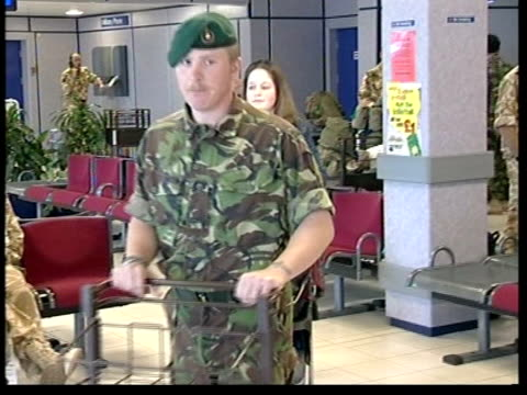 british soldiers return home: anthony crouch; england: oxfordshie: raf brize norton: int crouch along pushing luggage trolley followed by leanne... - day26 stock videos & royalty-free footage