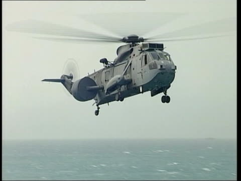 day 4 1830 evening news itn generics ext air view hms ark royal at sea sea king helicopter landing on deck - ark stock videos and b-roll footage