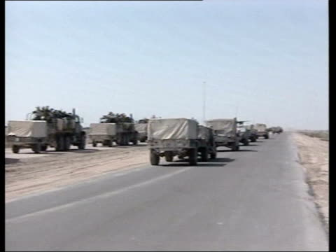 day 4 news at nine iraq nassiriya us military trucks driving away up road pan to soldier manning field gun to side of road - nasiriyah stock-videos und b-roll-filmmaterial