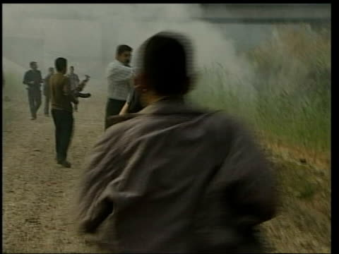 day 4 news at ten 2245 john irvine baghdad itn for itv iraq baghdad crowds of iraqi men on banks of river tigris iraqi soldiers on boat along as look... - itv news at ten stock-videos und b-roll-filmmaterial