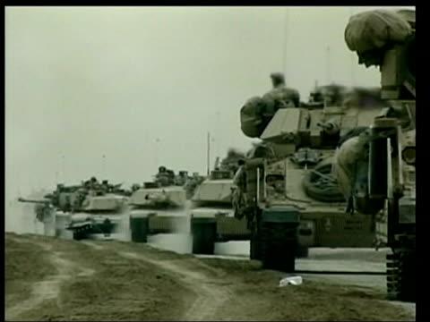 vidéos et rushes de news at ten; 22.45: robert moore - us prisoners of war convoy of armoured vehicles stopped on road tank seen thru heat haze tgv line of vehicles on... - irak