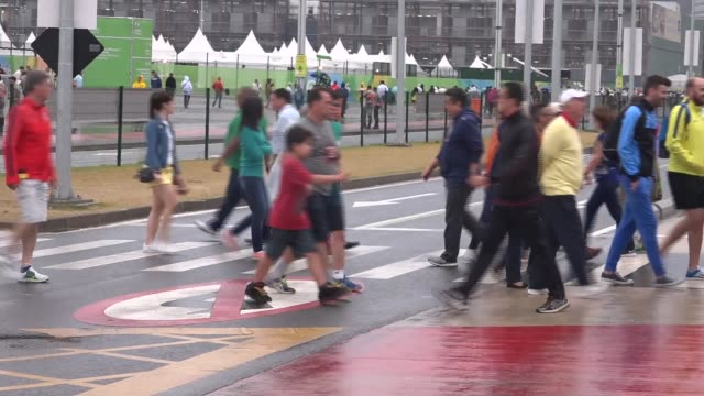 day 5: bad weather; brazil: rio de janeiro:olympic park: ext rain falling into large puddle / various of people along under umbrellas and through the... - day 5 stock videos & royalty-free footage