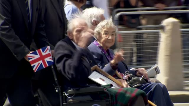 service of remembrance and parade **music heard sot** elderly man and woman waving as being pushed along in wheelchairs veterans and others along... - remembrance day stock videos and b-roll footage