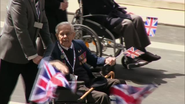 service of remembrance and parade **music heard sot** veteran in wheelchair waving hands and flags as along veterans in wheelchairs saluting as along... - remembrance day stock videos and b-roll footage