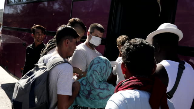 a day after a fatal fire killed at least two and clashes between asylum seekers and police took place asylum seekers prepare to board buses that will... - flüchtlingslager stock-videos und b-roll-filmmaterial