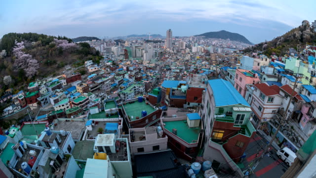 day and night view of ami tombstone cultural village (where houses are built on tombstones during korean war) and downtown district with cherry blossoms, busan, south korea - koreakriget bildbanksvideor och videomaterial från bakom kulisserna