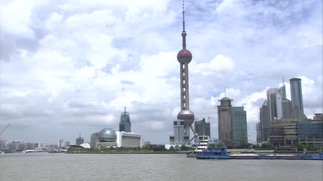 day and night views of shanghai barges along tilt up aurora building / boats along in harbour / people along promenade / buildings around harbour /... - crane stock videos & royalty-free footage