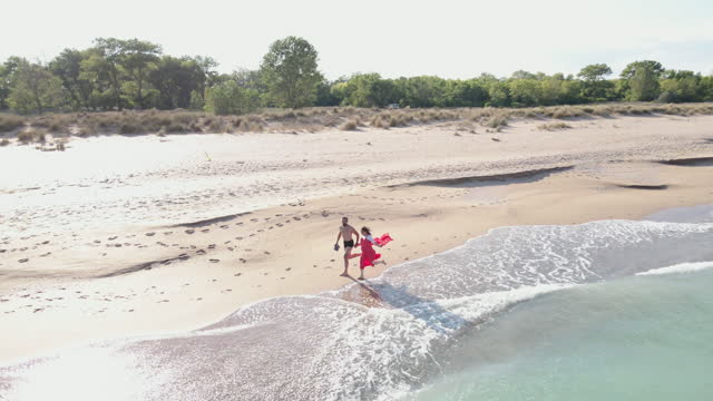 a day at the sea. aerial view of a couple in love walking on the beach, woman dressed in a red dress with a beautiful red scarf blown by the wind. romance and summer vacations at the sea. relationship, love and romance. - cruise collection stock videos & royalty-free footage