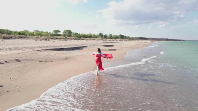 a day at the sea. aerial view of a young woman walking on the beach, dressed in a red dress with a beautiful red scarf blown by the wind. romance and summer vacations at the sea. - cruise collection stock videos & royalty-free footage