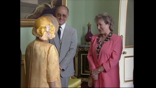 vidéos et rushes de buckingham palace celebrations; england: london: buckingham palace: int queen mother into room where she chats with guests including holness and... - harry secombe