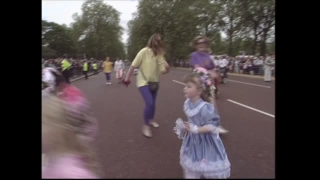 buckingham palace celebrations england london buckingham palace ext may day dancers along mall children in brightly coloured costumes along and thru... - medallist stock videos & royalty-free footage