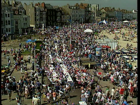 ltgv mass street party along promenade zoom in people sitting at tables and waving flags - street party stock videos and b-roll footage