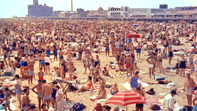 stockvideo's en b-roll-footage met day crowded coney island beach; sunbathers,umbrellas,etc. (period 1958) - zonwering