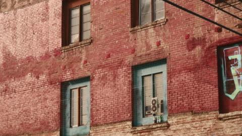 vidéos et rushes de day exterior decaying brick warehouse with graffiti - délabré