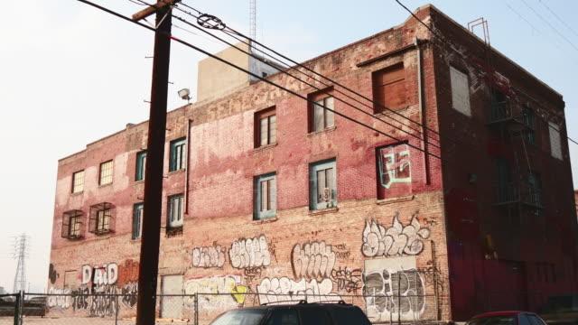 day exterior decaying brick warehouse with graffiti - zurückgelassen stock-videos und b-roll-filmmaterial