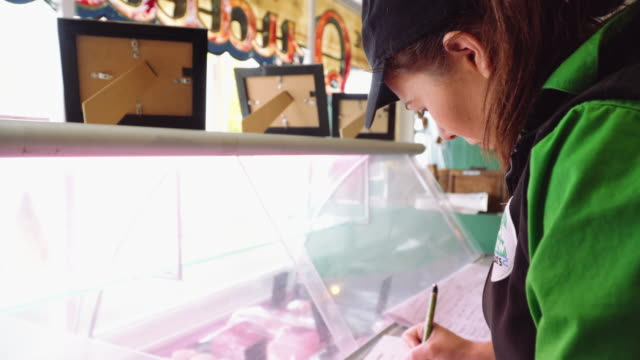 vídeos de stock e filmes b-roll de a day in the life of a butcher: woman writing down - um dia na vida de